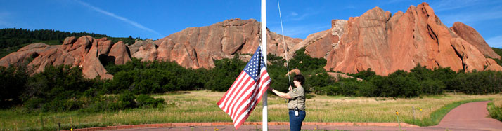 Parks staff raising US flag at Roxborough State park
