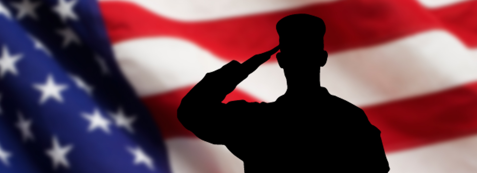 Person in military uniform saluting the United States flag.
