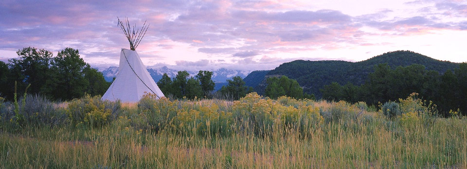 teepee in tall grass with mountains and sunset in background
