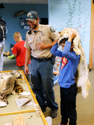 An interpreter at Barr Lake State Park shows a child animal furs, feathers, and turtle shells.