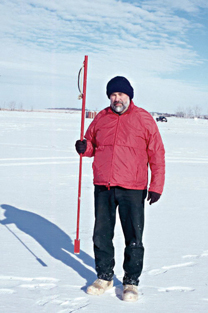 A fisherman stands with an ice chisel. Photo credit North Dakota Game & Fish Dept.
