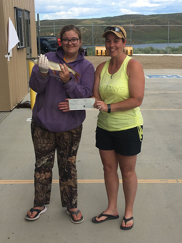 Female angler holding small northern pike. Second female holding winning check from 2020 tournament.