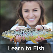 Young woman smiling and holding up the fish she caught