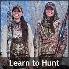 Two smiling young women in hunting gear