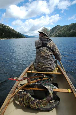 Bowhunter canoeing across lake.