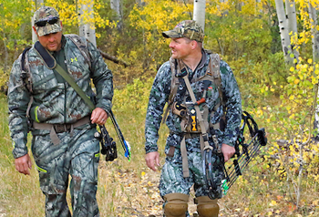 Two bow hunters in camo walking in the forest