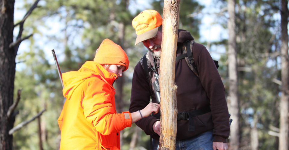 A mentor teaches a youth hunter about tracking.