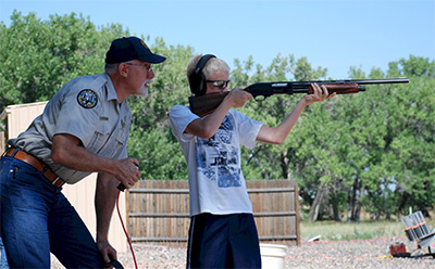 Area Wildlife Manager Mark Leslie coaches a young shooter at a Novice Hunter shooting clinic.