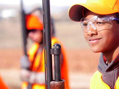 Boy smiling while waiting to shoot during the Novice Hunter Program at Wellington SWA.