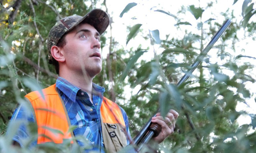 Hunter Kevn Lansing taking cover behind trees while dove hunting