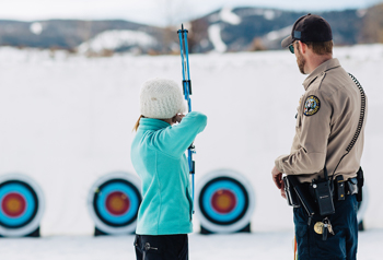 CPW employee teaching a young woman archery posture
