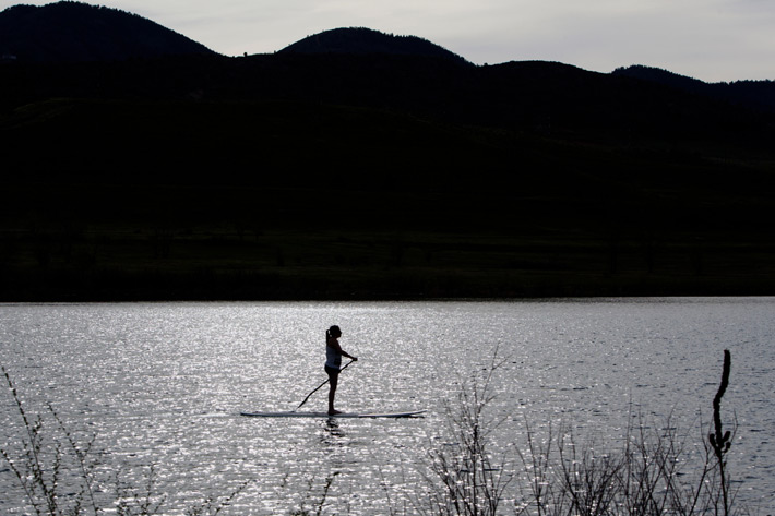 black and white image of woman on paddleboard with hills in background