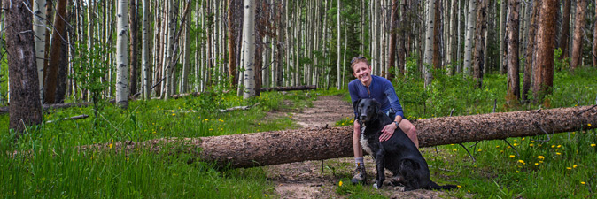 A hiker poses against a forest backdrop with a dog