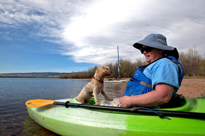 A small dog in a kayak with the owner.