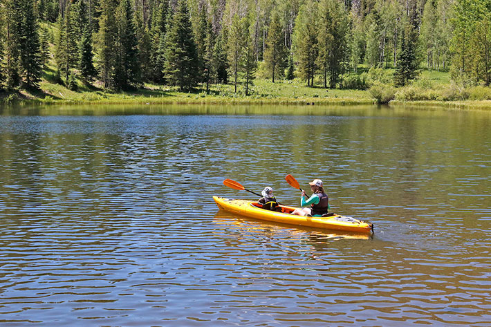 Mom and daughter kayaking on lake with trees and mountains in background