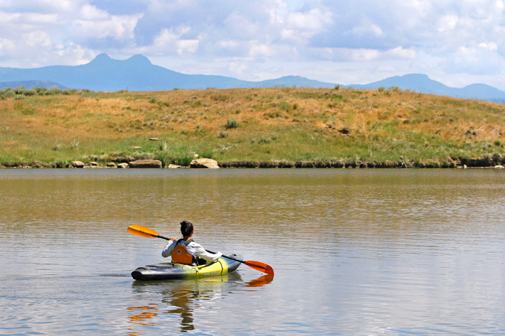 woman kayaking with mountain backdrop