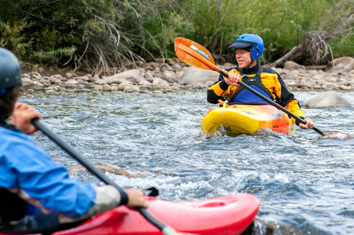 Men in helmets kayaking on river
