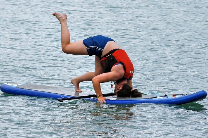 woman in life vest going into headstand on paddle board