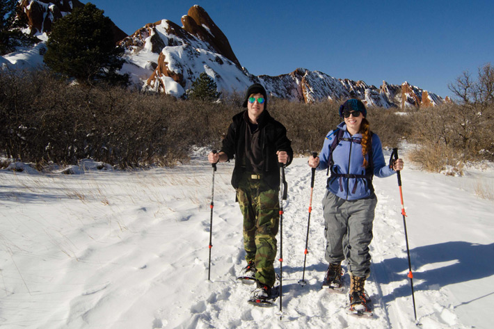 two people on snowshoes with glasses and hats