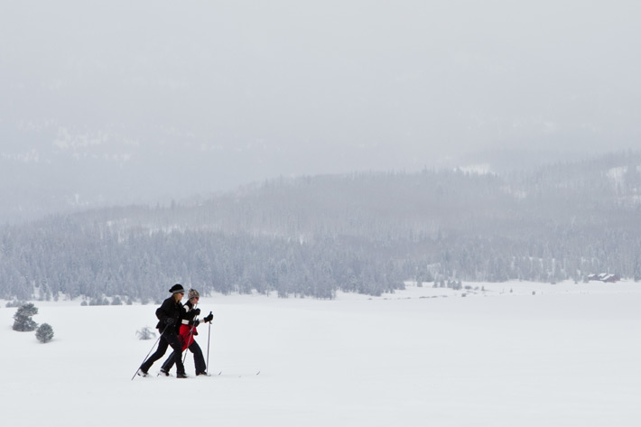 Two people skiing as it snows