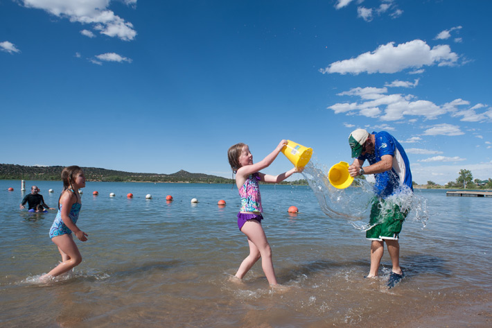 a family splashes in the lake with buckets