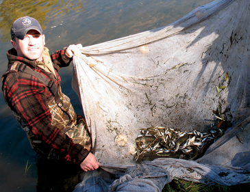 Aquatic research scientist Ryan Fitzpatrick with fishing net.