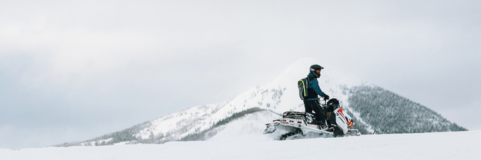 Snowmobiler in front of mountain.
