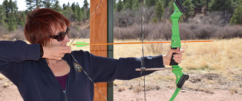 Alicia Cohn aiming a bow
