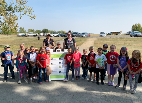 A group of school children and their chaperones pose next to a sign about the 7 leave no trace principles.